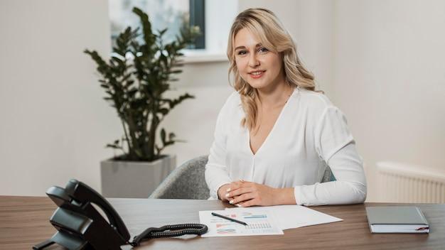 Vooraanzicht vrouw, gekleed in wit overhemd op kantoor