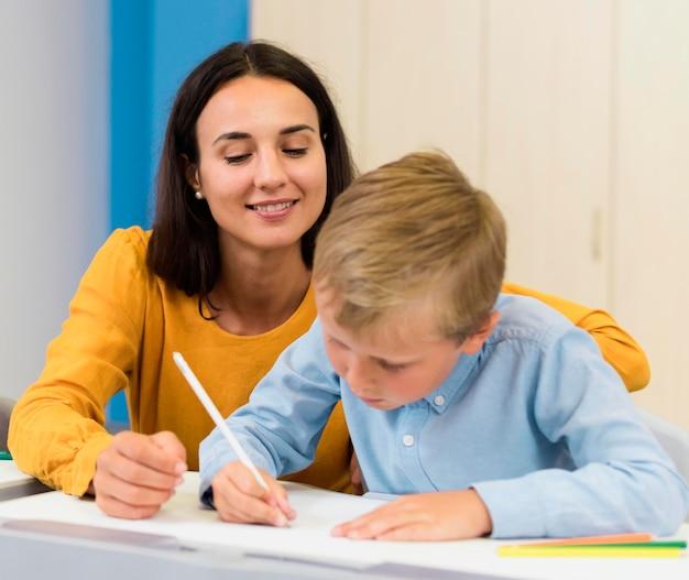 Vooraanzicht vrouw haar student helpen in de klas