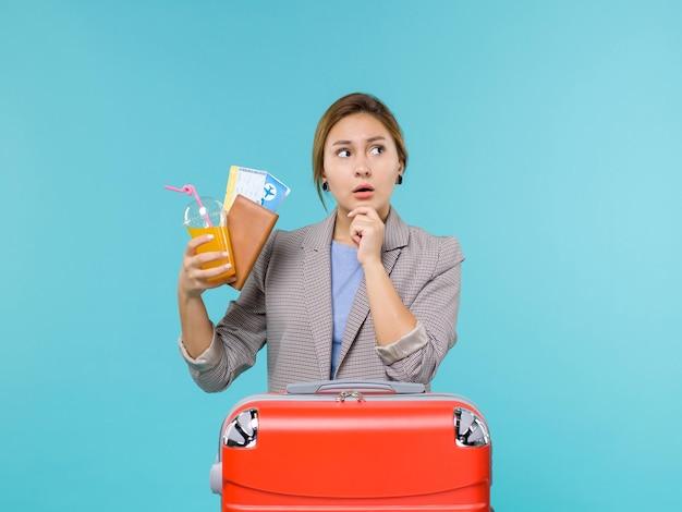 Vooraanzicht vrouw in vakantie bedrijf drankje en kaartjes op lichtblauwe achtergrond zeereis vakantiereis reizen