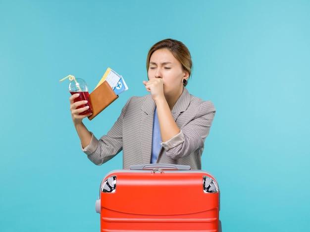 Vooraanzicht vrouw in vakantie bedrijf sap met kaartjes hoesten op de blauwe achtergrond reis reis vakantie reizen watervliegtuig