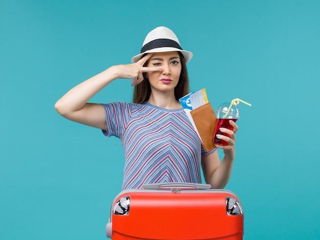 Vooraanzicht vrouw in vakantie bedrijf sap met kaartjes op lichtblauwe achtergrond reis reis vrouwelijke zee zomer vliegtuig