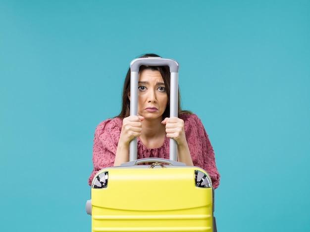 Vooraanzicht vrouw in vakantie met haar grote gele tas op de blauwe achtergrond reis zomer reis vrouw zee mens