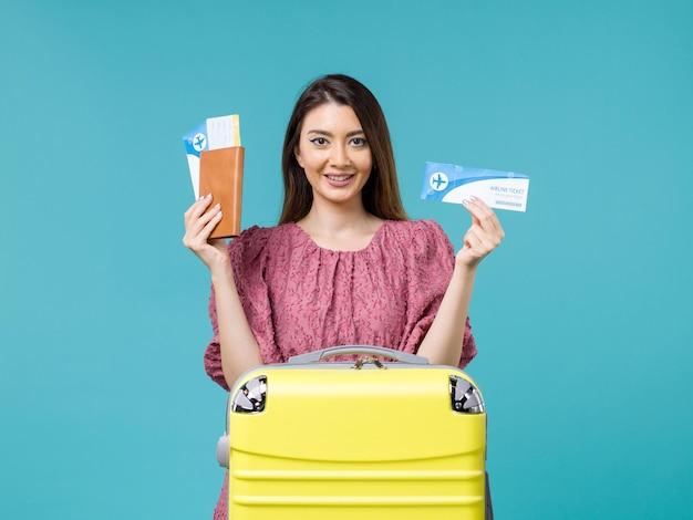 Vooraanzicht vrouw in vakantie met haar kaartjes op de blauwe achtergrond reis zee vrouw reis vakantie zomer
