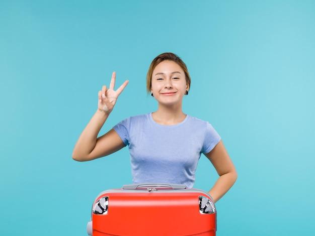 Vooraanzicht vrouw in vakantie met haar rode tas lachend op de blauwe achtergrond vakantie vliegtuig reis reis zeereis