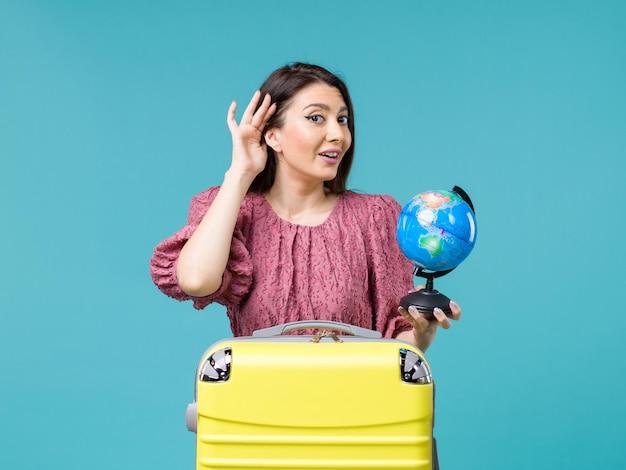 Vooraanzicht vrouw in vakantie met kleine aarde globe proberen te horen op blauwe achtergrond zee reis vrouw reis vakantie zomer