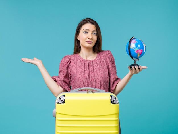 Vooraanzicht vrouw in vakantie met kleine wereldbol op blauwe bureau zee vakantiereis reis zomer vrouw