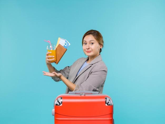 Vooraanzicht vrouw in vakantie met vers drankje en kaartjes op een lichtblauwe achtergrond zeereis vakantiereis reizen