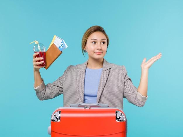 Vooraanzicht vrouw in vakantie met vers glas sap en kaartjes op lichtblauwe achtergrond reis vliegtuig vakantie reizen reis zee