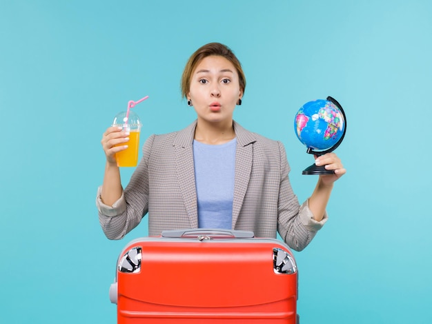 Vooraanzicht vrouw in vakantie met vers sap en globe op de blauwe achtergrond zee vakantie reis reis reis