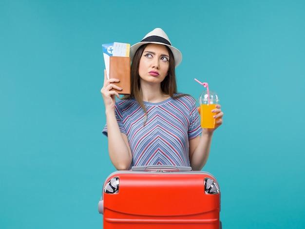 Vooraanzicht vrouw in vakantie met vers sap en kaartjes op lichtblauwe achtergrond reis reis reis vakantie zee zomer