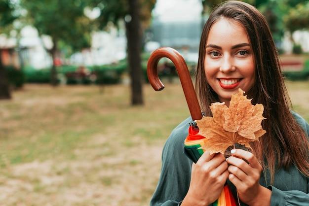 Vooraanzicht vrouw met bladeren en een paraplu met kopie ruimte