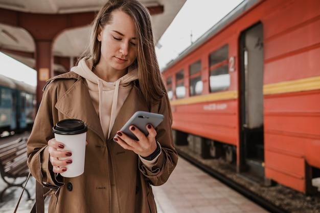 Vooraanzicht vrouw met een kopje koffie op het treinstation
