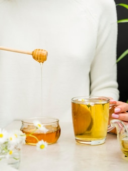 Vooraanzicht vrouw met honing dipper en glas met thee