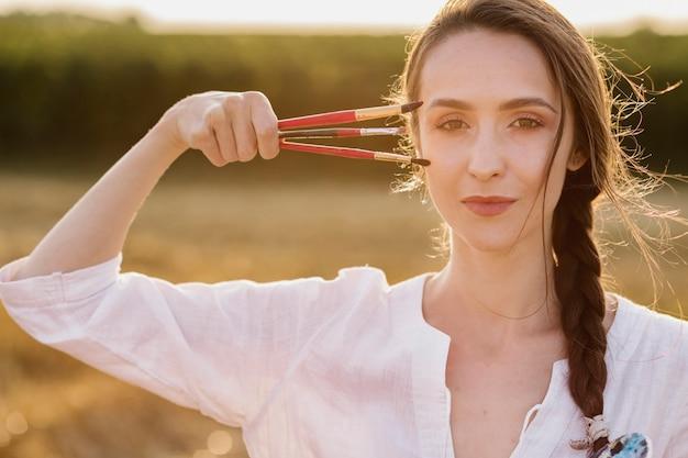 Vooraanzicht vrouw met verf penselen