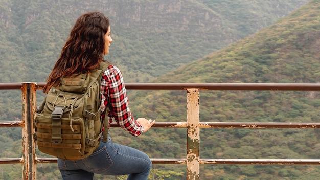 Vooraanzicht vrouw op brug bewonderen van de natuur