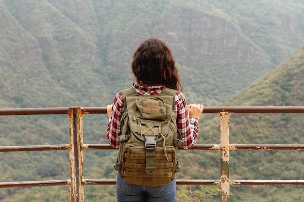 Vooraanzicht vrouw op brug kijken naar de natuur