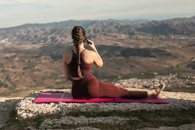 Vooraanzicht vrouw op yoga mat praten over de telefoon