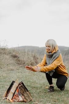 Vooraanzicht vrouw opwarming van de aarde bij kampvuur