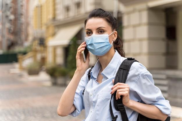 Vooraanzicht vrouw praten aan de telefoon met een gezichtsmasker op