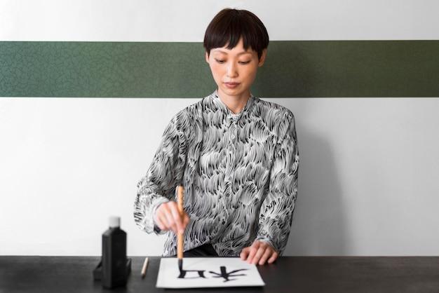 Vooraanzicht vrouw schilderij met penseel
