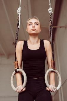 Vooraanzicht vrouw training op gymnastiek ringen