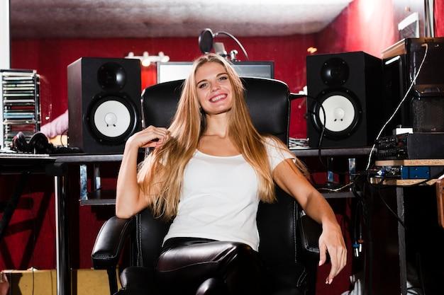 Vooraanzicht vrouw zitten en glimlachen in een recordstudio