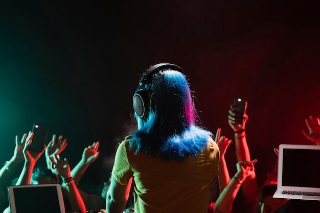Vooraanzicht vrouwelijk dj bij soundboard in club