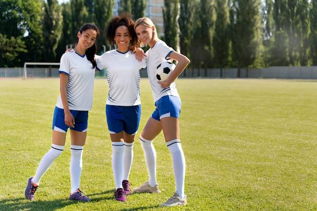Vooraanzicht vrouwelijk voetbalteam poseren