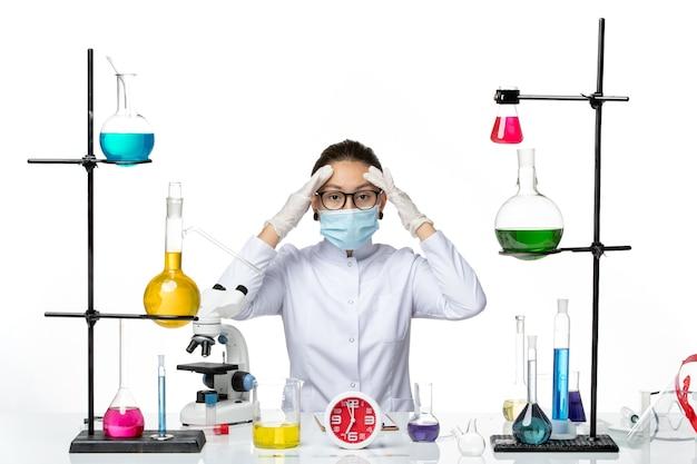 Vooraanzicht vrouwelijke apotheker in medisch pak met masker zittend met oplossingen op de lichte witte achtergrond chemicus lab virus covid-splash