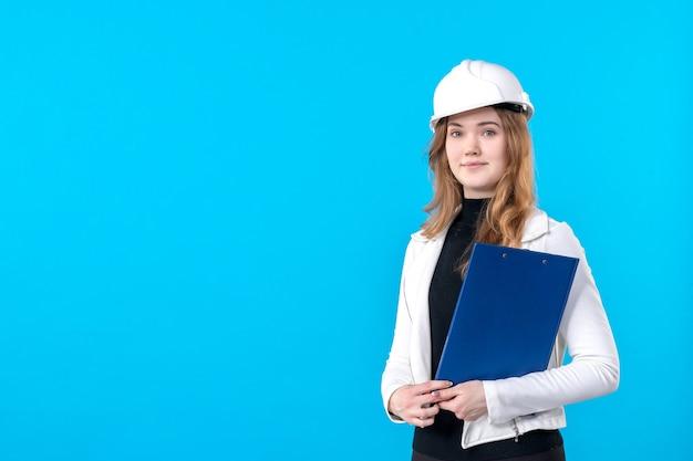 Vooraanzicht vrouwelijke architect die blauw dossierplan op blauw houdt