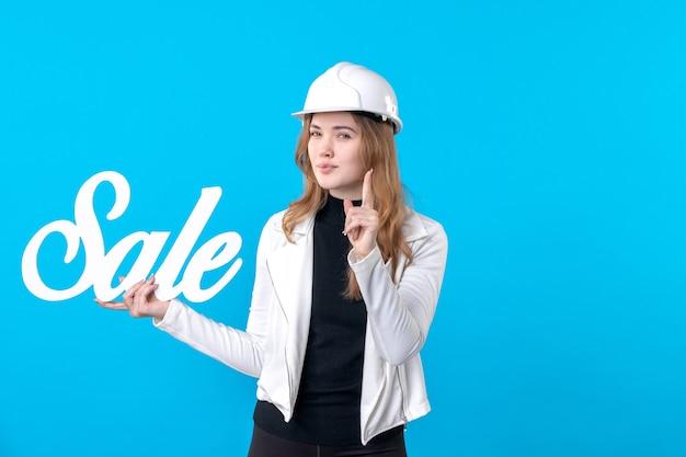 Vooraanzicht vrouwelijke architect die verkoopwaarschuwing op blauw houdt