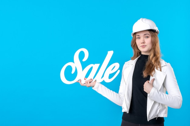 Vooraanzicht vrouwelijke architect die witte verkoop houdt die op blauw schrijft