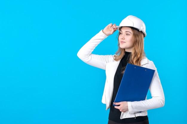 Vooraanzicht vrouwelijke architect in helm met blauw dossierplan op blauw