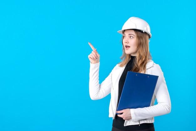 Vooraanzicht vrouwelijke architect in witte helm op blauw