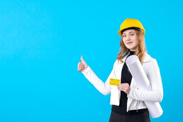 Vooraanzicht vrouwelijke architect met plan en bankkaart op het blauw