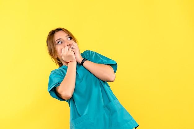 Vooraanzicht vrouwelijke arts bang op gele ruimte