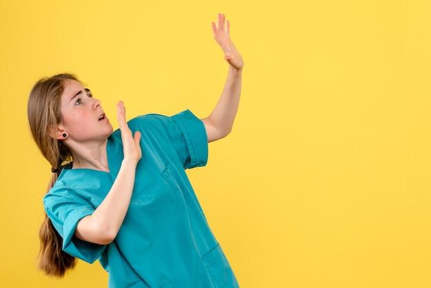 Vooraanzicht vrouwelijke arts bang voor iets op gele achtergrond gezondheid medic ziekenhuis emotie