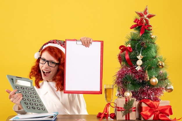 Vooraanzicht vrouwelijke arts bedrijf calculator rond kerstcadeautjes en boom