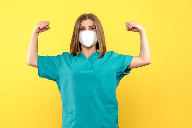 Vooraanzicht vrouwelijke arts buigen op gele ruimte