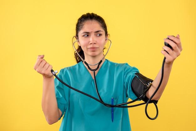 Vooraanzicht vrouwelijke arts die bloeddrukmeetapparaat houdt