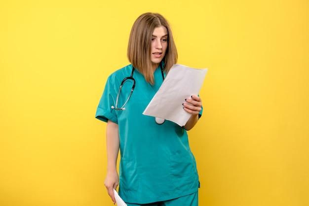 Vooraanzicht vrouwelijke arts die dossiers op gele ruimte leest