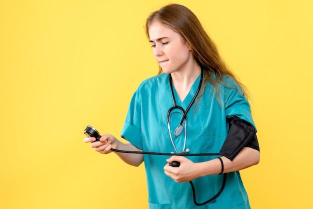 Vooraanzicht vrouwelijke arts die druk op de lichtgele arts van het achtergrondgezondheidsziekenhuis meet