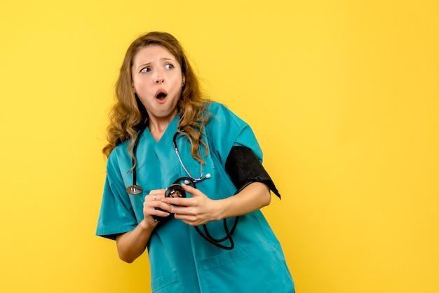 Vooraanzicht vrouwelijke arts die druk op gele de gezondheidsdokter van het vloerziekenhuis meet