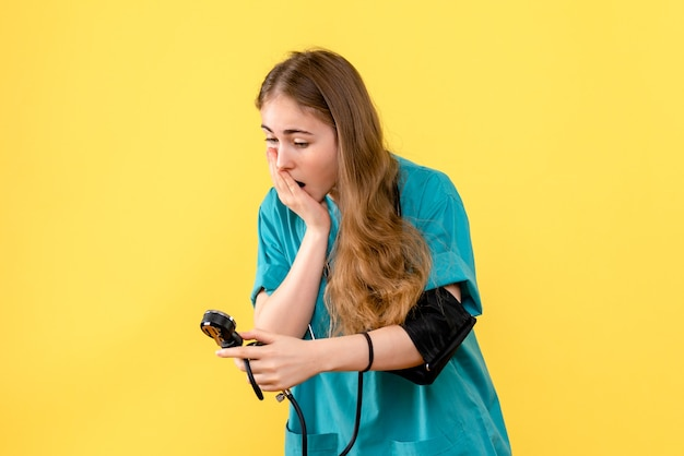 Vooraanzicht vrouwelijke arts die druk op gele het ziekenhuisdokter van de vloergezondheid meet