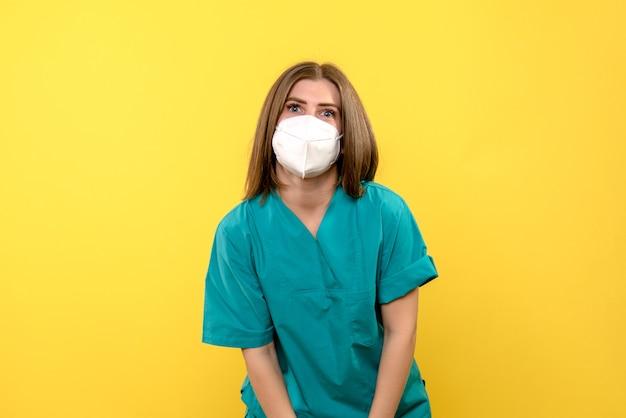 Vooraanzicht vrouwelijke arts die gewoon met masker op gele ruimte staat