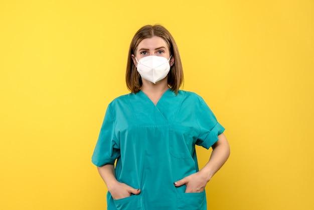 Vooraanzicht vrouwelijke arts die gewoon op gele ruimte staat