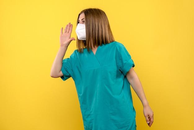 Vooraanzicht vrouwelijke arts die iemand op gele ruimte roept