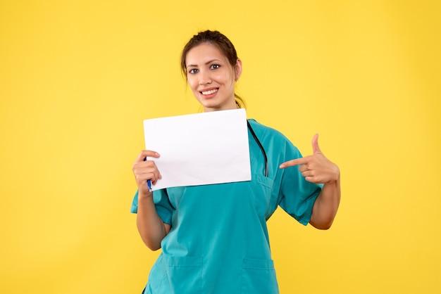 Vooraanzicht vrouwelijke arts die in medisch overhemd document analyse op gele achtergrond houdt