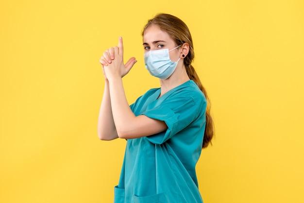 Vooraanzicht vrouwelijke arts die kanon imiteert die op gele achtergrond ziekenhuisgezondheid covid houdt