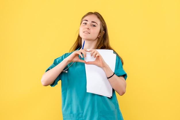 Vooraanzicht vrouwelijke arts die liefde op gele achtergrond het ziekenhuisverpleegster van het gezondheidsvirus verzendt